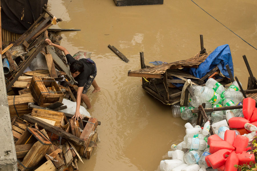 Photo of a man trying to gather scattered possessions in the wake of a flood.