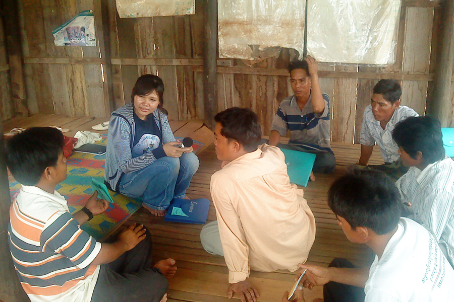 Photo of a woman interviewing Cambodian businesspeople.