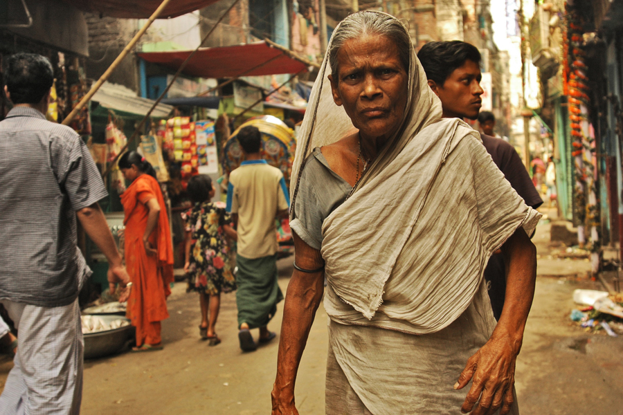 Photo of a woman walking through the streets of India.