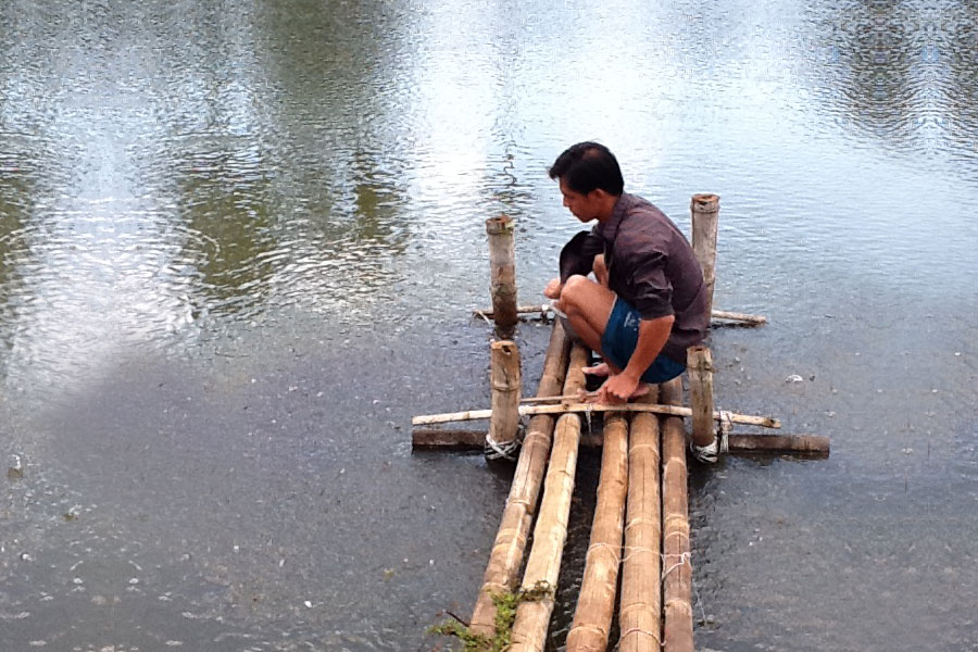 Photo of a man tending to a fish farm.