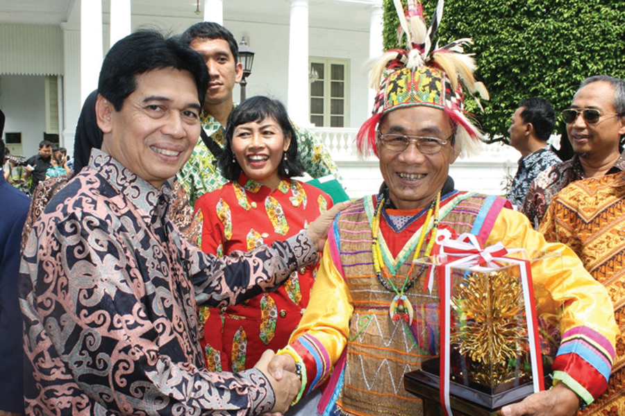 Photo of a handshake between representatives of the indigenous Dayak people of Wehena and the local government of East Kutai.