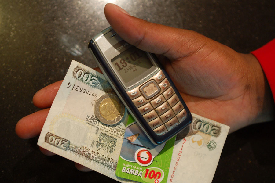 Photo of a hand holding a mobile phone, cash, and a calling card.